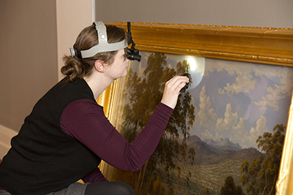 Jennifer O'Connell, Senior Conservator (Painting), condition checking a painting prior to installation in the National Picture exhibition